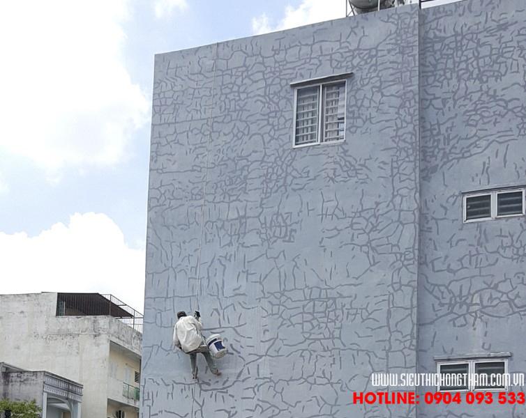 thợ chống thấm đang thi công tường ngoài nhà